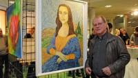 Der Kunstmaler Jörg Christian steht neben einem Gemälde, das die Mona Lisa zeigt.