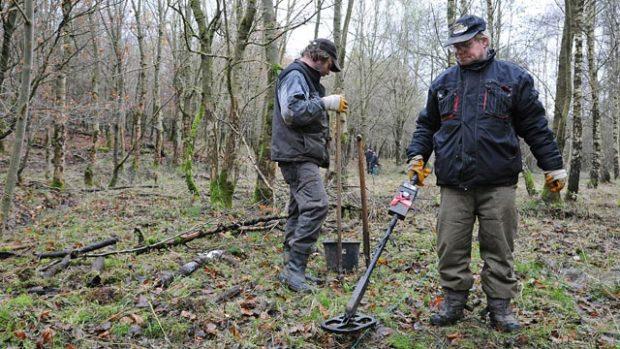 Mann mit Metallsonde in einem kahlen Wald