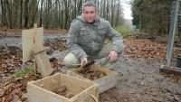 Knieender Mann zeigt verrottete Rste von Granaten in einer Kiste.