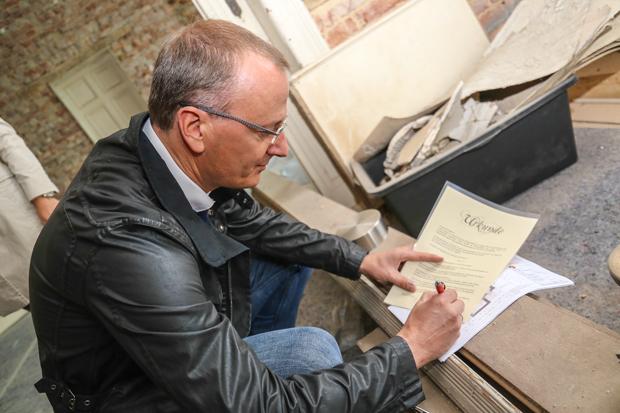 Ralf Bohn unterschreibt die Urkunde, die mit in die Zeitkapsel gesteckt wird.